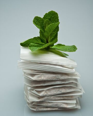 Leaves of mint and tea bags on a light background Stock Photo - 12686393