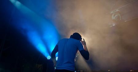 the DJ behind work in night club