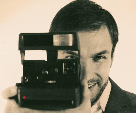 cheerful nice photographer with the camera in hands photographs photo