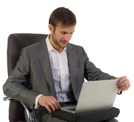 nice businessman works sitting in a chair with the open laptop Stock Photo - 18600755