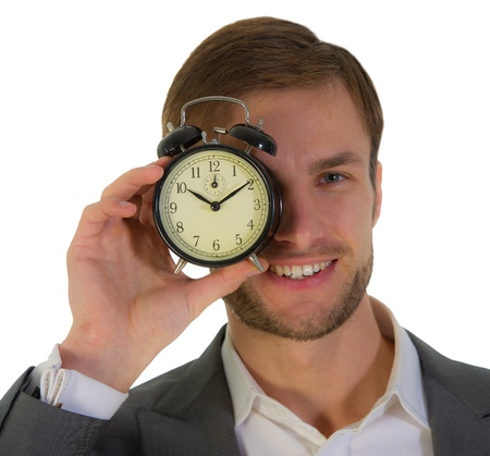 nice businessman with an alarm clock in a hand points to time, isolated on a white background photo