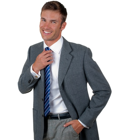 corrects: nice businessman corrects a hand a tie and smiles, isolated on a white background