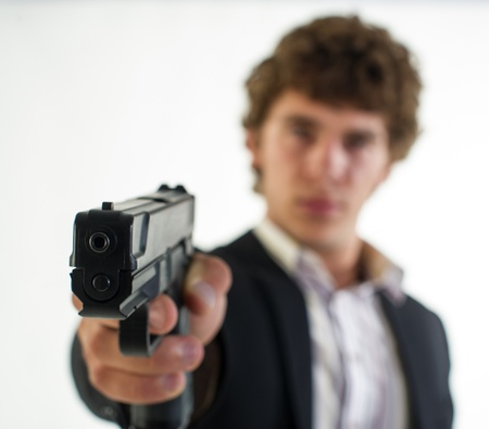 young man with the gun in a hand aims aside on a light background photo
