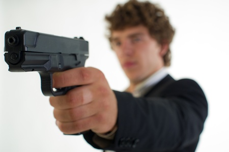 special service agent: young man with the gun in a hand aims aside on a light background