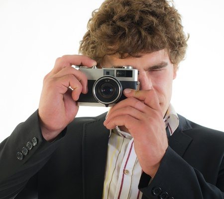 young photographer from old 35 mm the camera on a light background