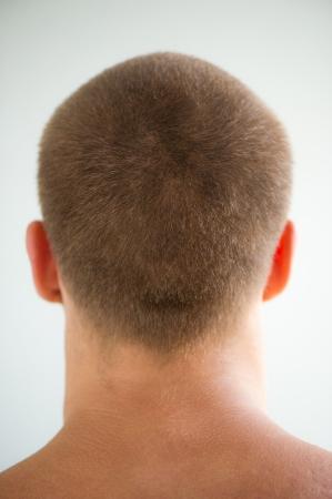 若い男は、明るい背景に短い毛直後の頭 写真素材