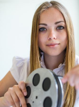 the girl looks the reel with the black-and-white picture at 16 mm to a film Stock Photo - 22296166