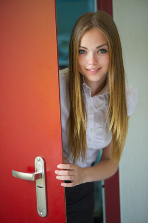 portrait of the beautiful woman with a flowing hair and an open door