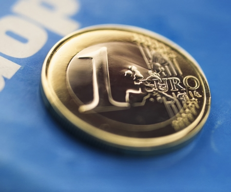 one euro coin against the back of blue paper closeup Stock Photo - 22732184
