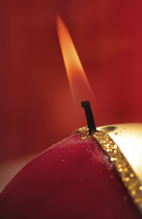 lit Christmas candle isolated on red photo