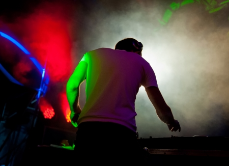 DJ working on the background lighting effects at the disco photo
