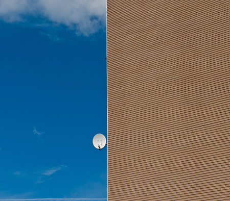 satellite antenna on the house wall against the blue sky on a sunny day photo