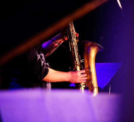 man playing the saxophone in the concert hall photo
