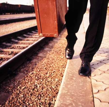 feet businessman walks along the railroad and in the hands of an old suitcase photo