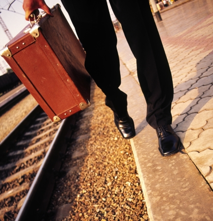 jetsetter: feet businessman walks along the railroad and in the hands of an old suitcase