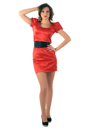 corrects: Woman posing  Beautiful young girl in red dress corrects hair standing
