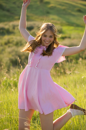 Beautiful girl in a pink dress with her hair dancing in nature, the summer season  photo