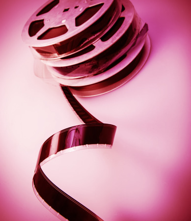 old reel of film of 16 mm on a pink  photo