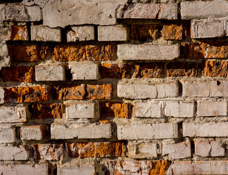 old brick wall partially destroyed and covered with cracks