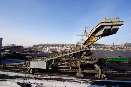 open trench: loading iron ore conveyor machine from the warehouse, mining production