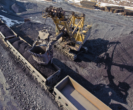 open cast mine: loading of iron ore wagons excavated from a warehouse