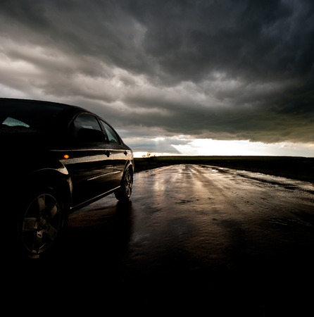 car on the road with wet asphalt on the background of a stormy sky photo