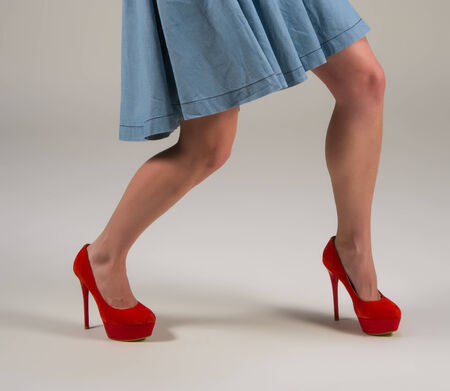 Female legs and red shoes on a light background photo