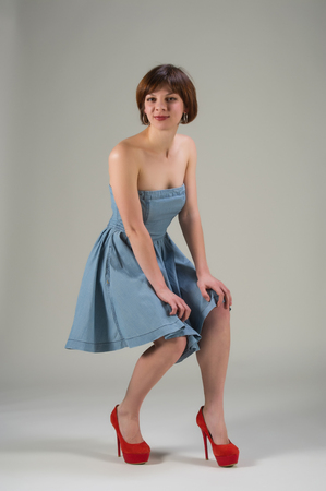 crouched: cute young woman in denim dress and red shoes in a pose on a light background