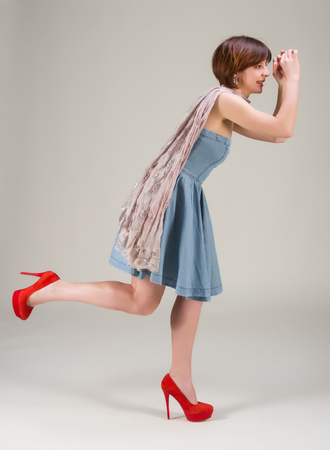 cute young woman in denim dress and red shoes and scarf  photo