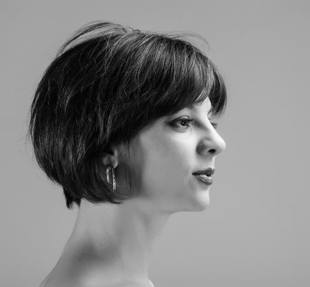 portrait of a pretty young woman with short hair on a light background in profile, 30 years old  photo