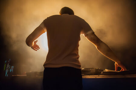 live DJ music in a nightclub on a background of light effects photo
