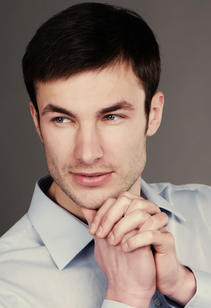 Portrait of a young businessman stares and holds his hand on his chin photo