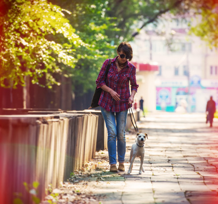woman walking with a pet in the city park