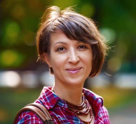 portrait of pretty woman on a background of city park, aged 40 Standard-Bild