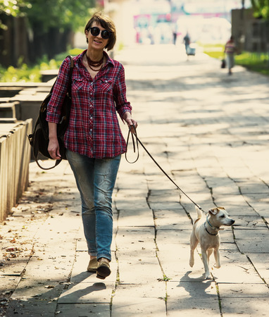 woman walking with a pet in the city park photo