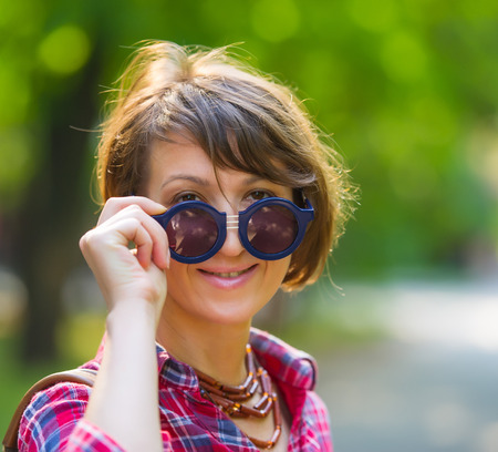 age forty: portrait of a pretty woman in sunglasses on background of city park, age forty to forty-five years Stock Photo