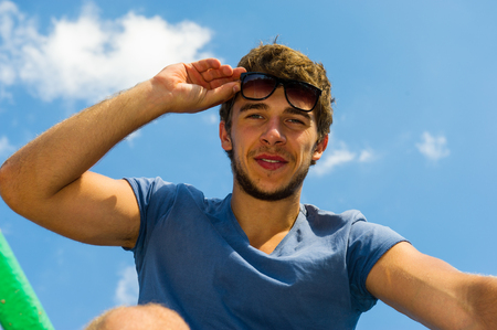 cute guy: Portrait of cute guy in glasses on a background of blue sky
