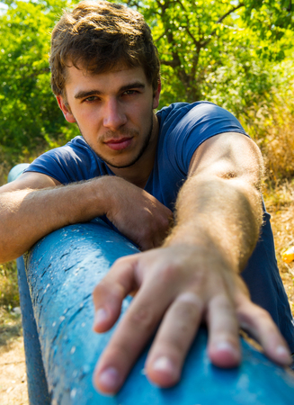 cute guy: portrait of a cute guy on a background of green plants