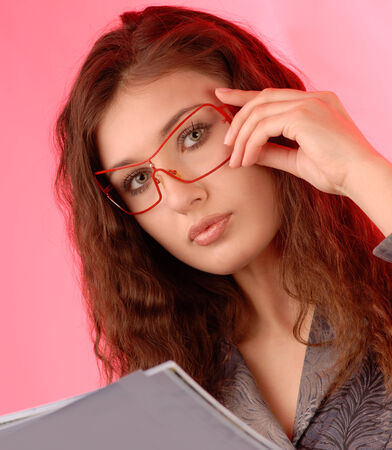 portrait of a beautiful young woman in glasses on pink background photo