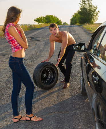 man helps a woman to replace the wheel on the car photo