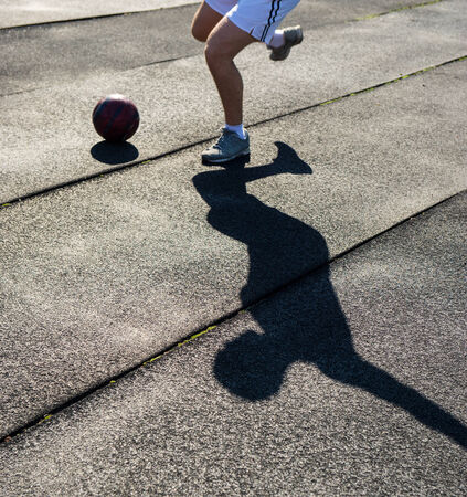 athlete with the ball and shadow on a dark background photo