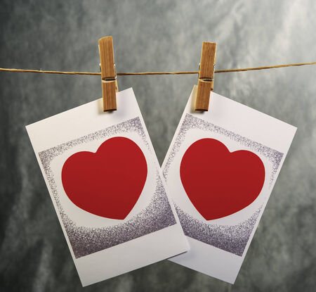 Valentine heart symbol on the photos pinned on clothesline photo