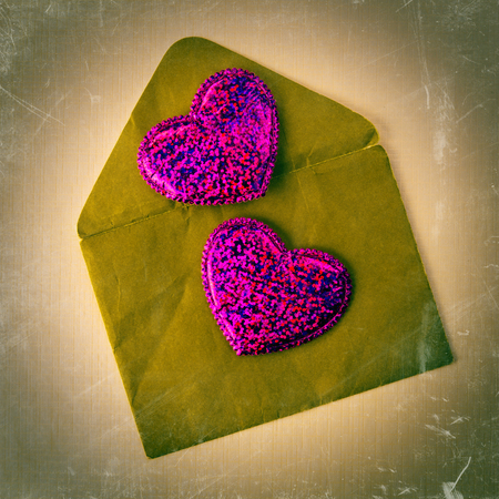 Two hearts lie on the hard old envelope. Valentine photo