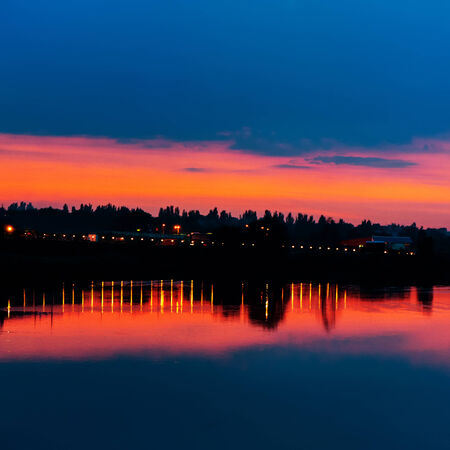Evening city lights in the background of sky and lake, the summer season photo