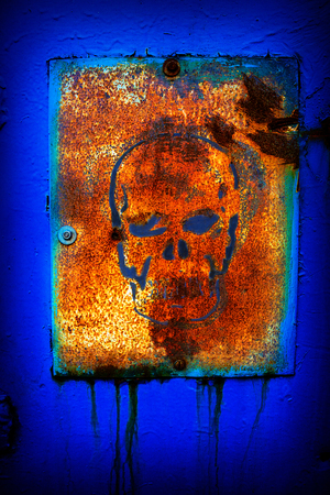 old rusty metal sign with a skull painted on the wall photo
