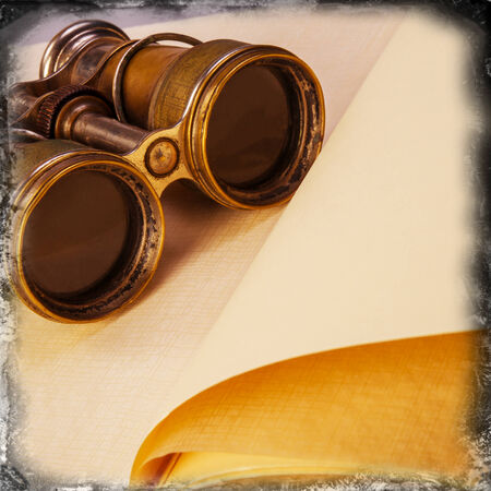 antique binoculars: old binoculars on an open book
