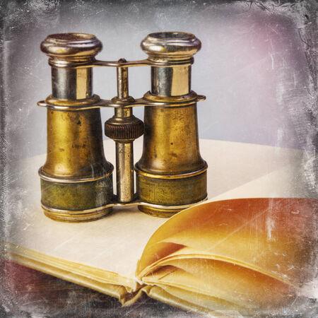 antique binoculars: old binoculars on an open book