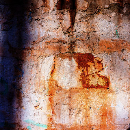 old brick wall covered with cracked plaster photo