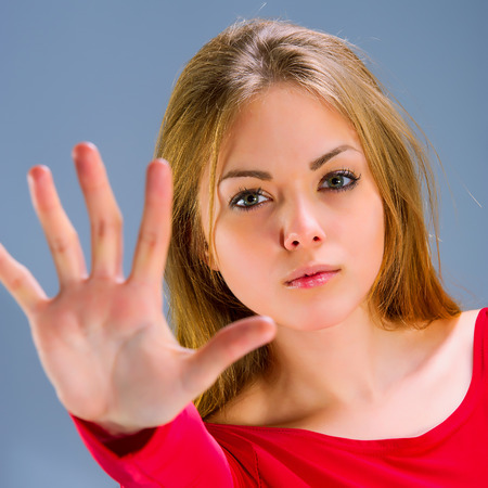 Young Woman Showing Stop Hand Gesture in stuidio