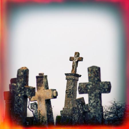 Old terrible stone cross on cemetery on background of sky, autumn season photo